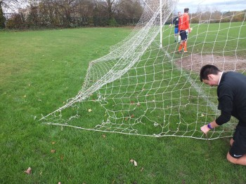 The referee examines the net, which clearly has several hole.