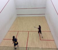 University of Lincoln's women's team cmpetitor againt one of the members of the Anglia Ruskin Squash team